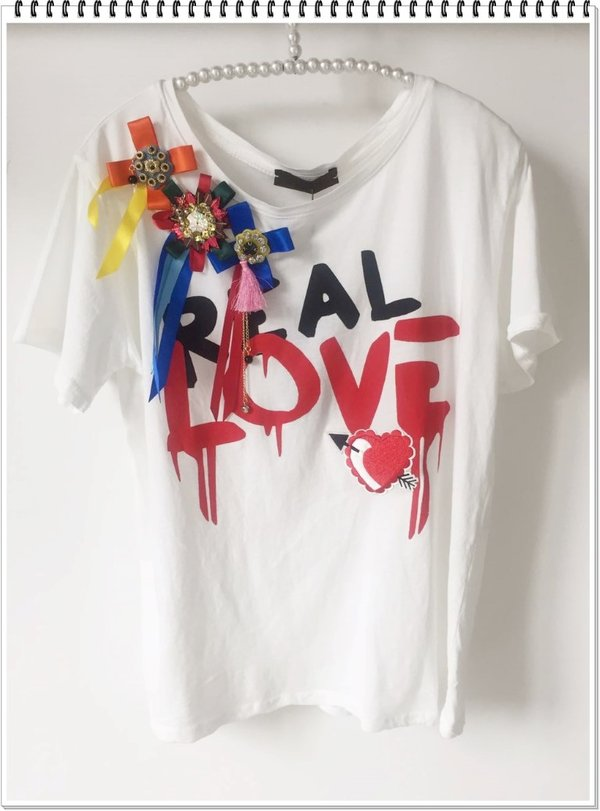 T-shirt real love con coccarde colorate.