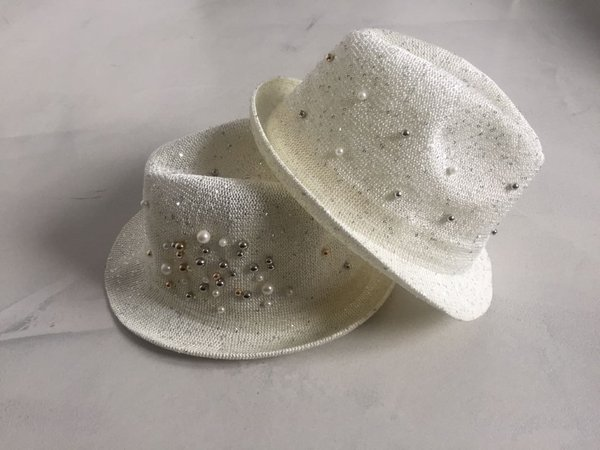 Cappello in rete con lurex perle e borchie applicate.