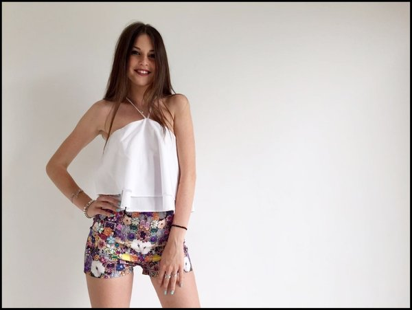 Crop top bianco su short in fantasia con pietre colorate applicate.