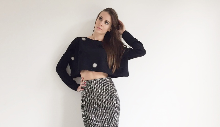 Longuette in paillettes bicolore e crop top con pon pon in visone.