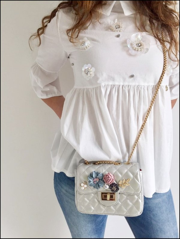 Camicia con fiori applicati, mini bag tracolla con fiori colorati e jeans corto.