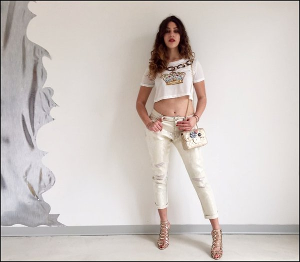 Jeans strappi in paillettes beige con mini t-shirt corona e mini bag con fiori applicati.